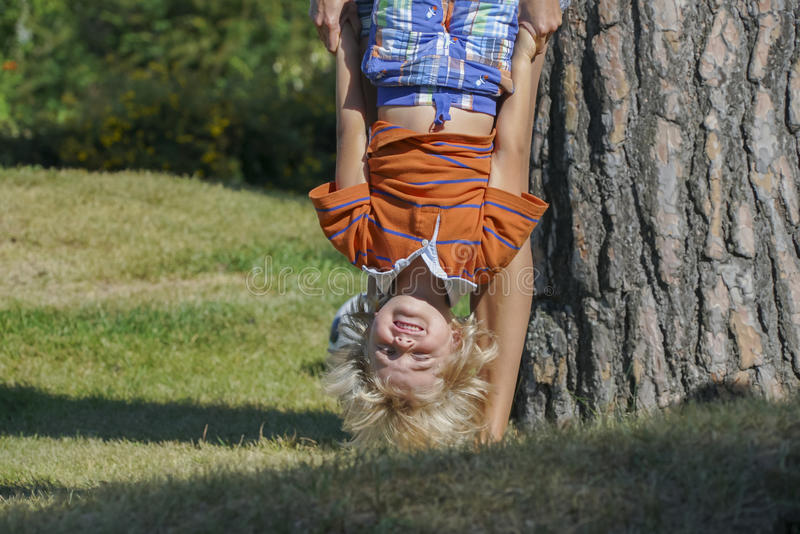 Happy kid playing upside down outdoors. Little boy playing upside down with his mother near the tree in the park stock photos