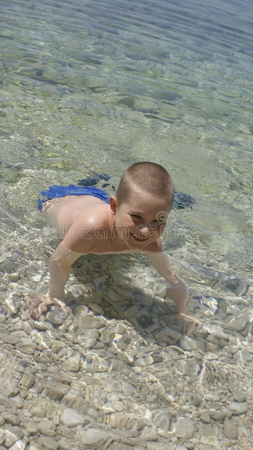 Happy kid playing in water stock photography