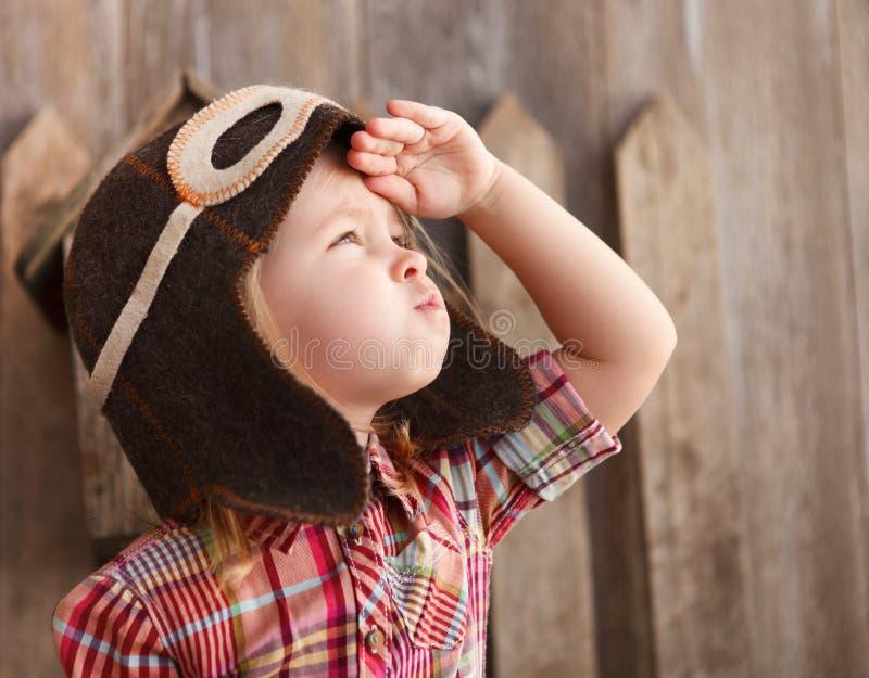 Happy kid playingin pilot helmet. Near the wooden background royalty free stock image