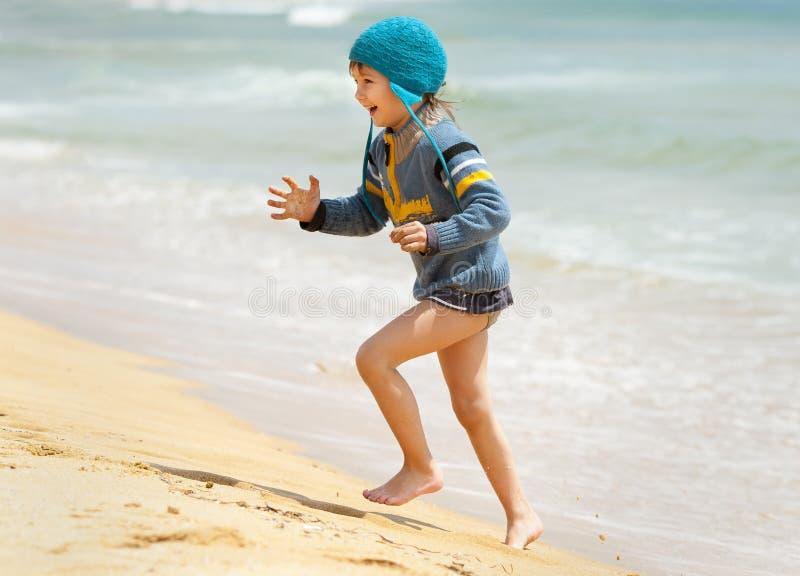 Happy kid running on the sea beach stock photos