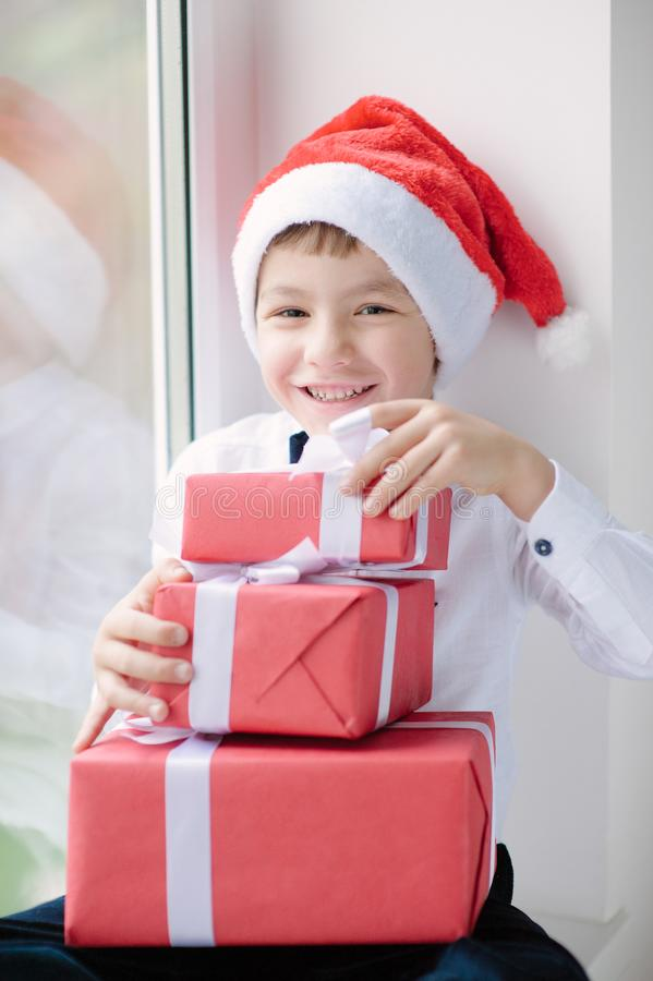 Boy in santa hat sit near the window and holds gifts stock images