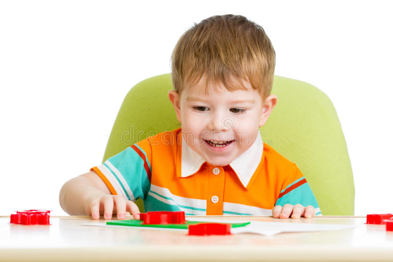 Happy kid sitting at table and playing stock images