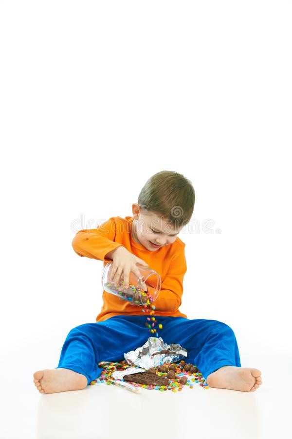 Happy kid spilling sweets on the floor sitting. Happy cute kid spilling sweets on the floor from glass jar sitting. Isolated on white stock photos