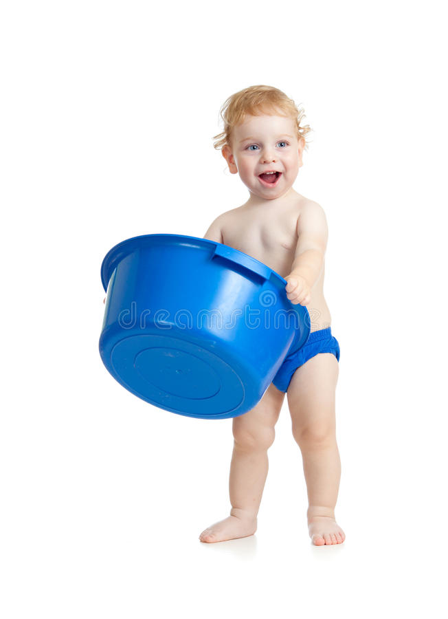 Happy kid standing with plastic wash bowl stock photography