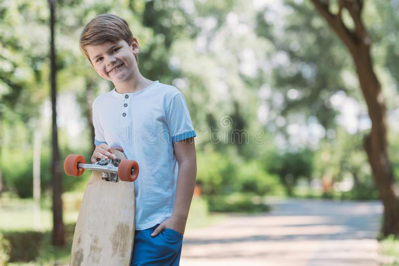 happy kid standing with skateboard and smiling at camera in park royalty free stock images