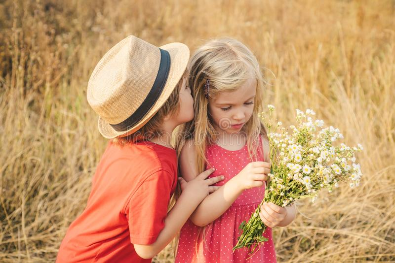 Happy Kid on summer field. Happy children girl and boy hug on meadow in summer in nature. Human emotions - kids first stock image