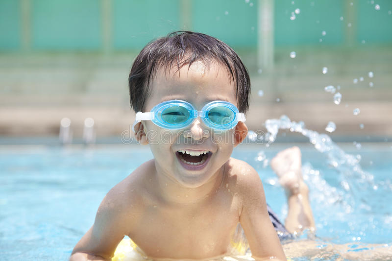 Happy kid in swimming pool. Asian Boy in Swimming Pool royalty free stock photos