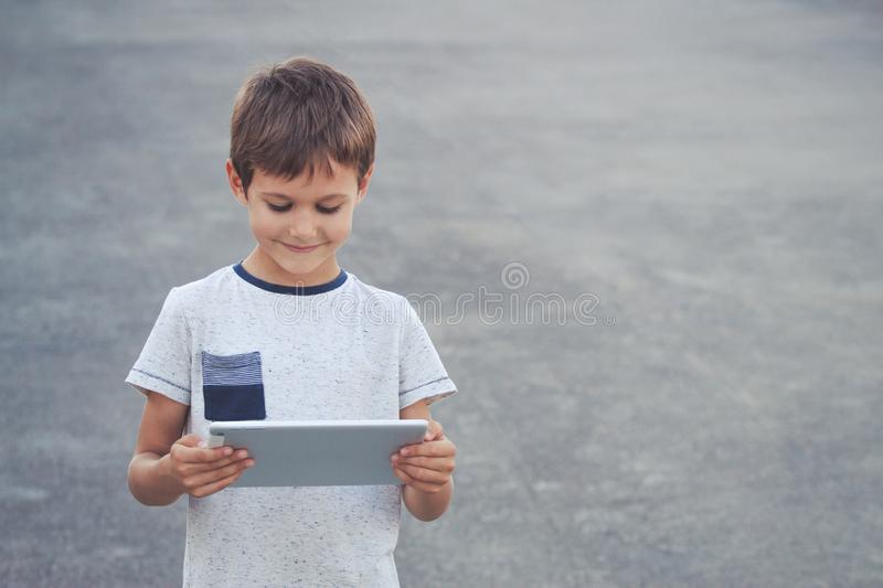 Happy kid with tablet computer outdoors royalty free stock images