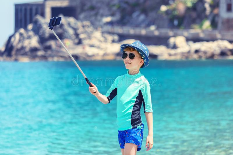 Happy kid taking selfie at beach, smiling little boy having fun in vacation on tropical sea sharing picture on social media stock image