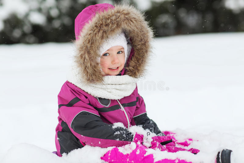 Happy kid in winter clothes playing with snow stock photo