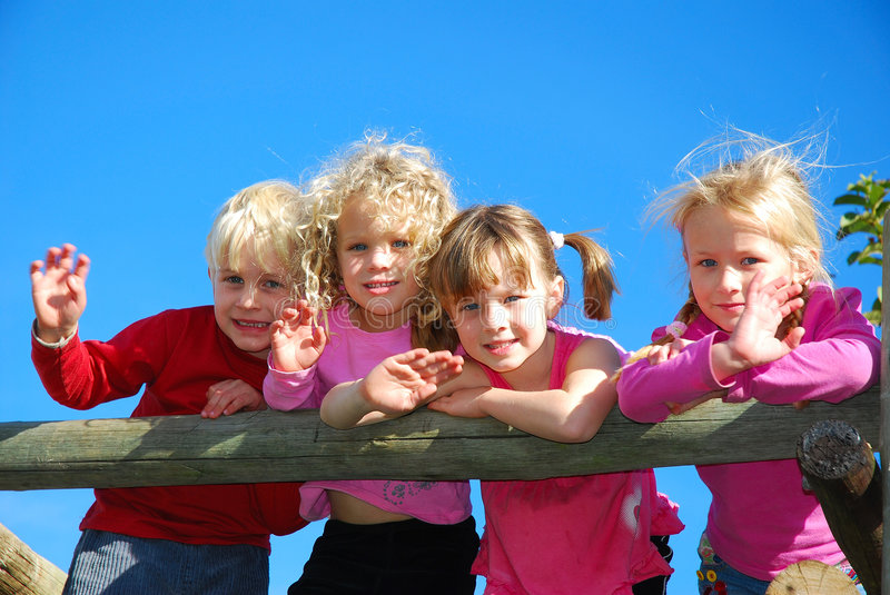 Happy kids. Four caucasian white children (one blond boy and three girls) with blue eyes standing on the playground and watching outdoors