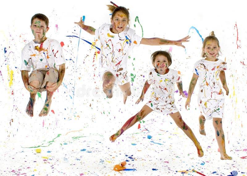 Happy Kids. Children jumping in paint splattered studio
