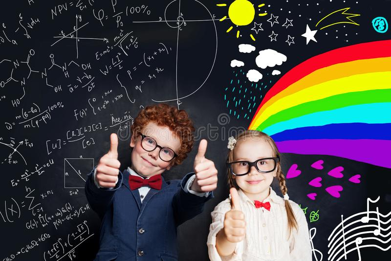 Happy kids against school chalkboard background. Back to school concept stock photography