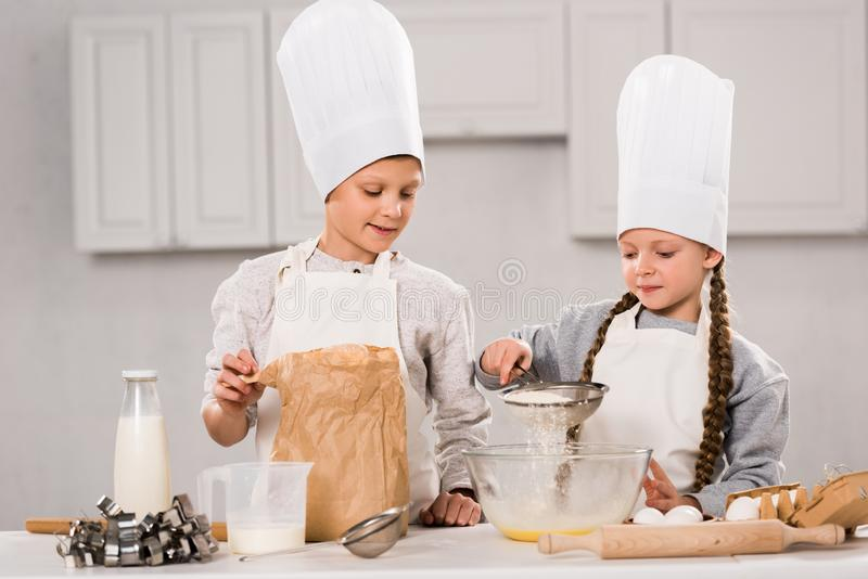 Happy kids in aprons sifting flour through sieve into bowl at table. In kitchen royalty free stock photo
