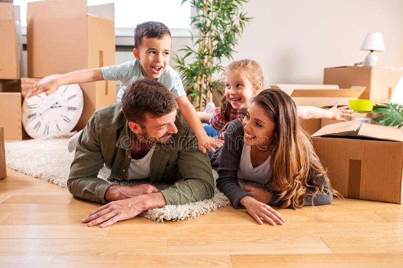 Happy kids on the back of their parents stock image
