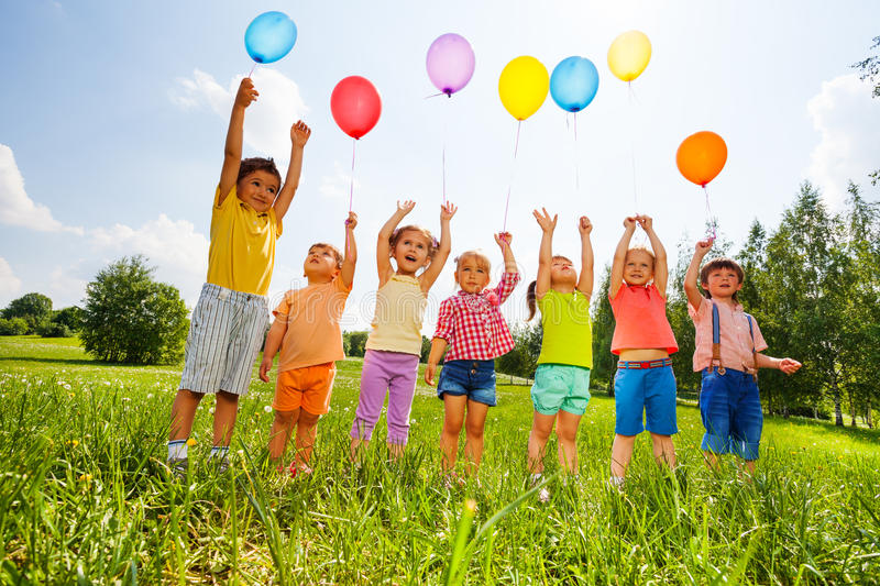 Happy kids with balloons and arms up in the sky royalty free stock photos