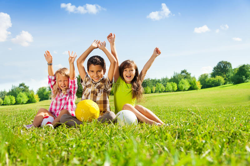 Happy kids with balls and lifted hands royalty free stock photos
