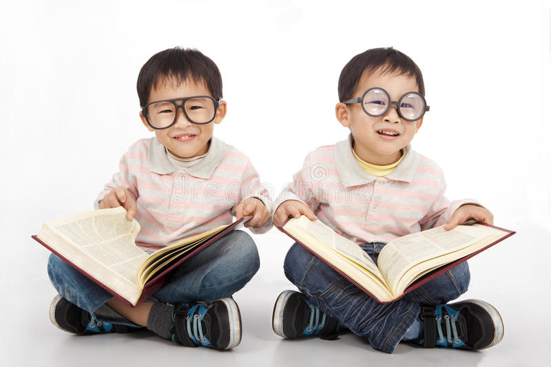 Happy kids with big book. Wearing black glasses royalty free stock photos