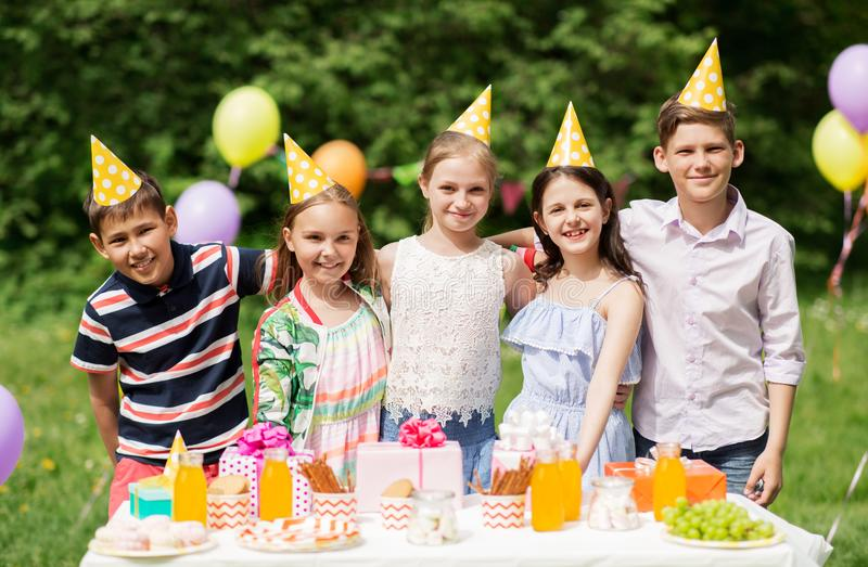 Happy kids on birthday party at summer garden. Holidays, childhood and celebration concept - happy kids hugging on birthday party at summer garden stock image