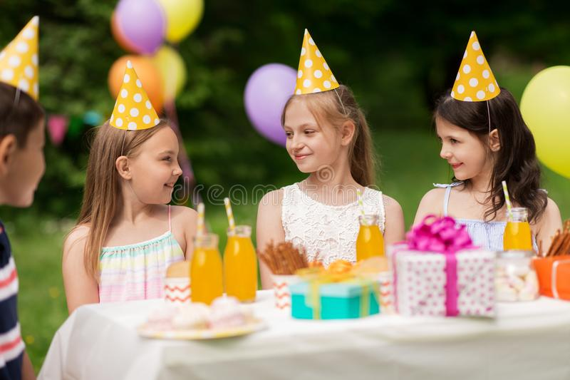 Happy kids on birthday party at summer garden. Holidays, childhood and celebration concept - happy kids sitting at table on birthday party at summer garden stock photography