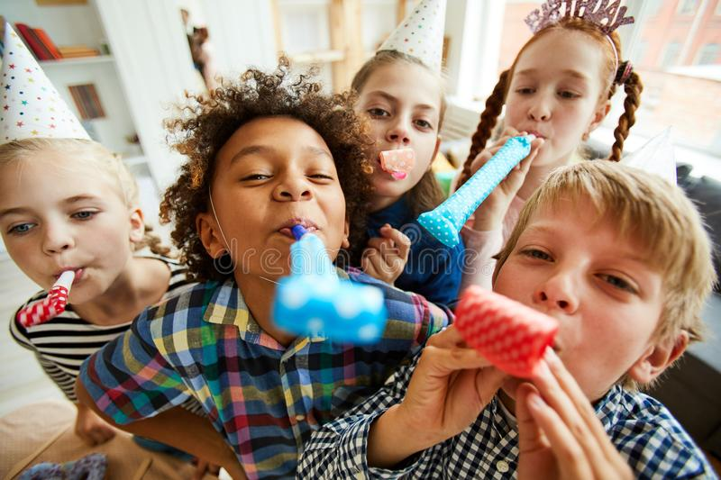 Happy Kids Blowing Party Horns stock image