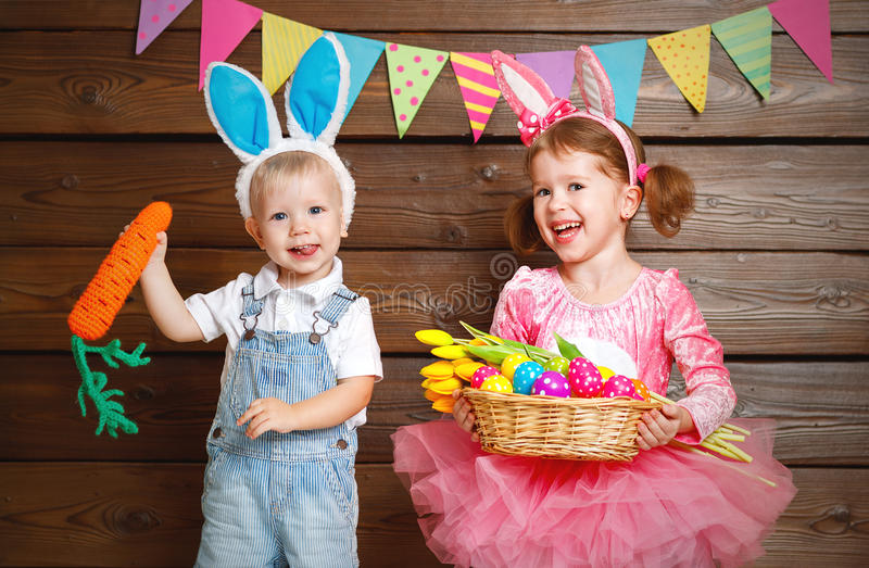 Happy kids boy and girl dressed as Easter bunnies with basket of stock image