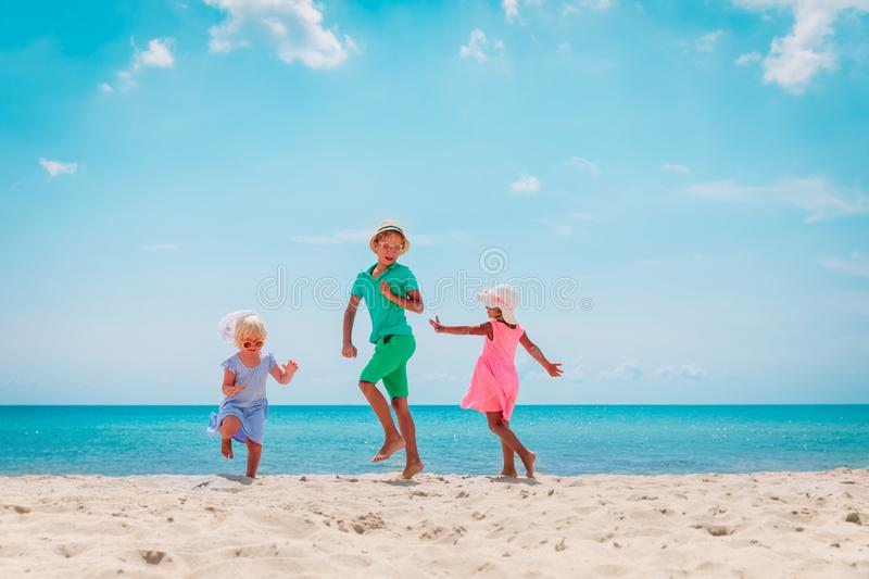 Happy kids- boy and girls- dance at beach, family enjoy vacation at sea. Happy kids- boy and girls- dance at tropical beach, family enjoy vacation at sea stock images