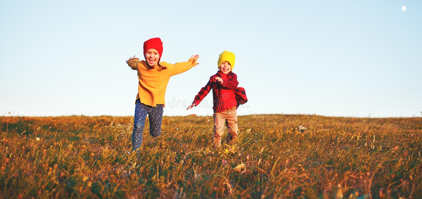 Happy kids   boy and girl running and laughing on autumn nature walk royalty free stock photo