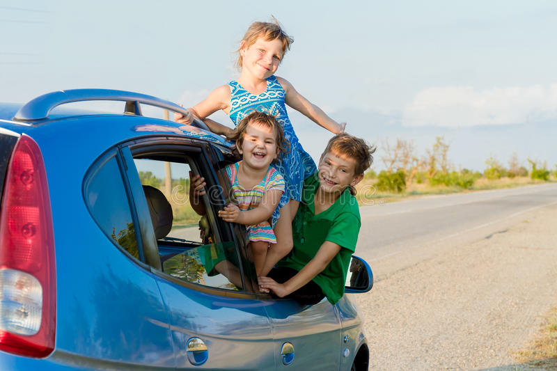 Happy kids in car, family trip, summer vacation travel. Three happy kids in car, family trip, summer vacation travel stock photo