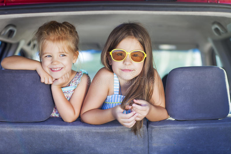 Happy kids in the car. Family on vacation. Summer holiday and car travel concept stock photography