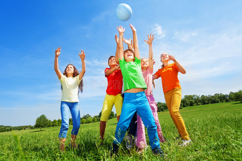 Happy kids catching ball in air outside. In summer stock images