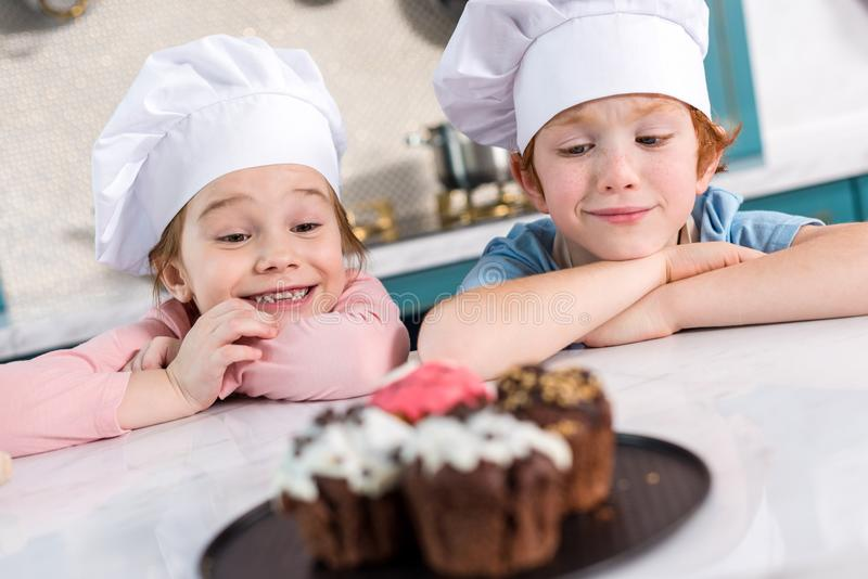 Happy kids in chef hats looking at delicious cupcakes. On foreground royalty free stock images