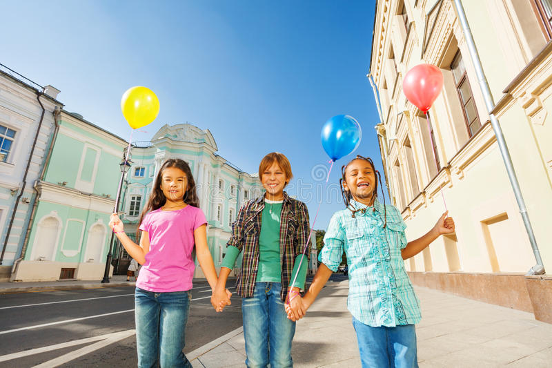 Happy kids with colorful balloons walking in city stock photography