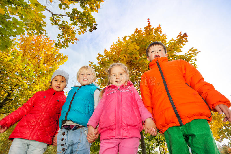 Happy kids in colorful jackets standing together stock image