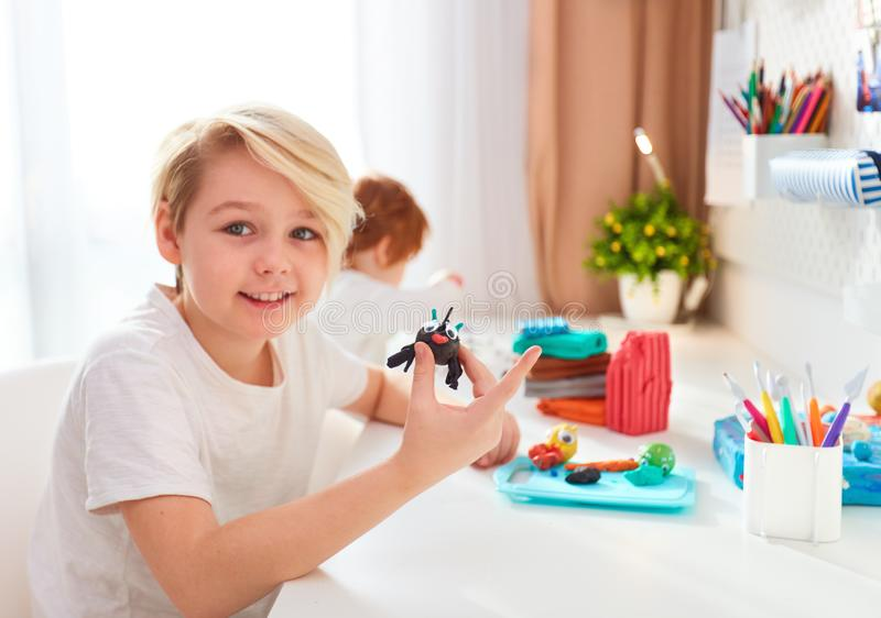 Happy kids are creating the hand crafts from modelling plasticine in the kids room royalty free stock photography