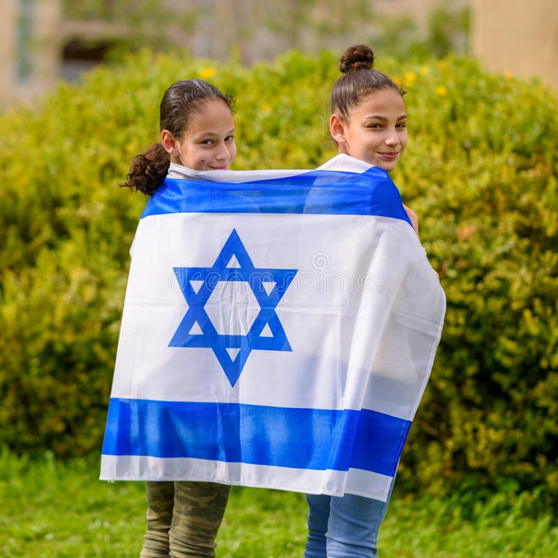 Happy kids, cute little teen girls with Israel flag. stock image