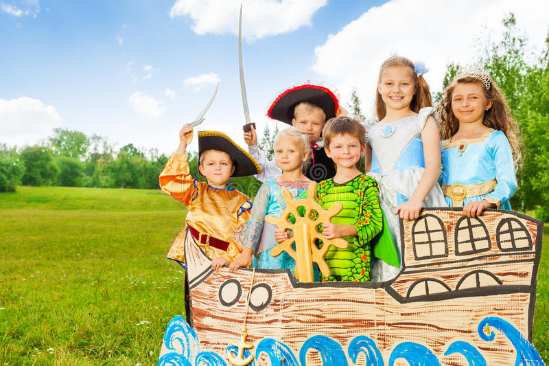 Happy kids in different costumes stand on ship royalty free stock images