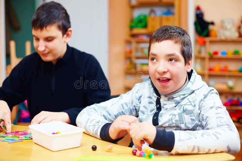 Happy kids with disability develop their fine motor skills at rehabilitation center for kids with special needs. Portrait of happy kids with disability develop stock photo