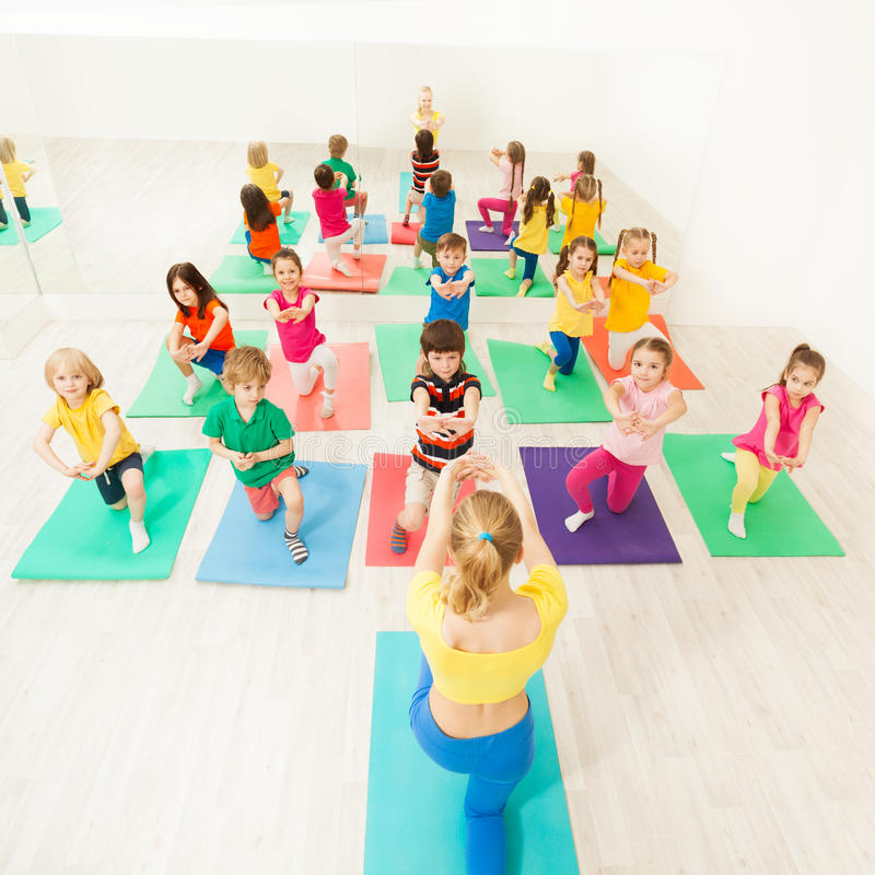 Happy kids doing kneeling exercises in gym stock photos