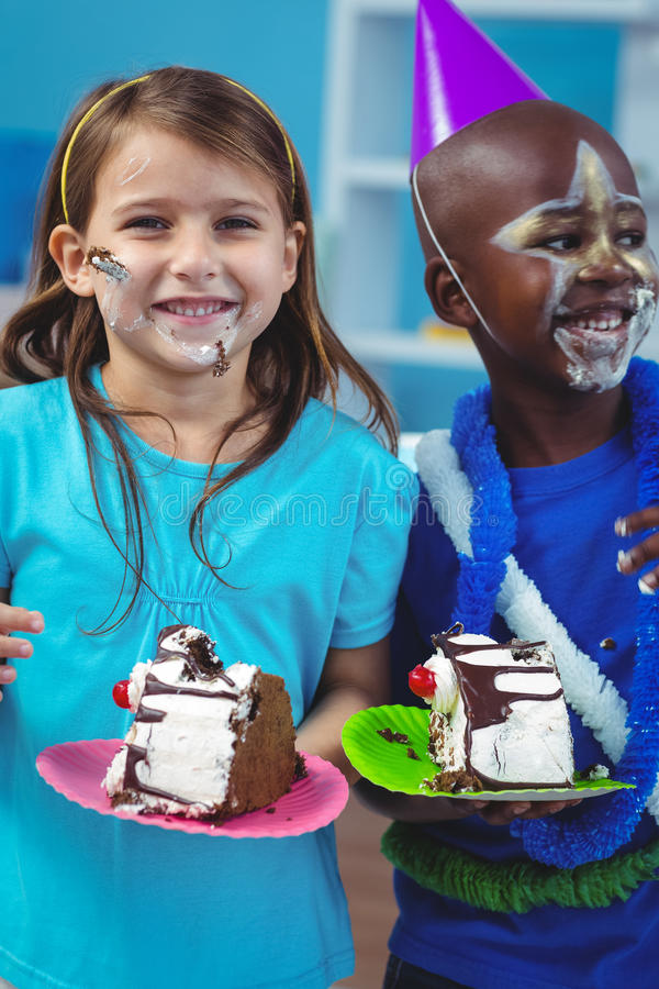 Happy kids eating birthday cake. At the birthday party stock photo