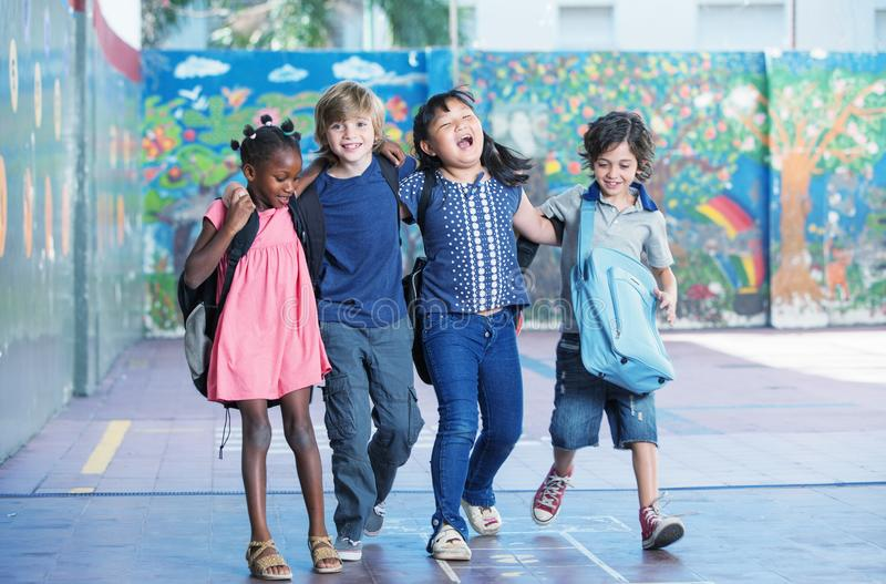 Happy kids embracing and smiling in the elementary schoolyard. I royalty free stock photos