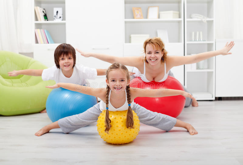 Happy kids exercising with their mother stock photography