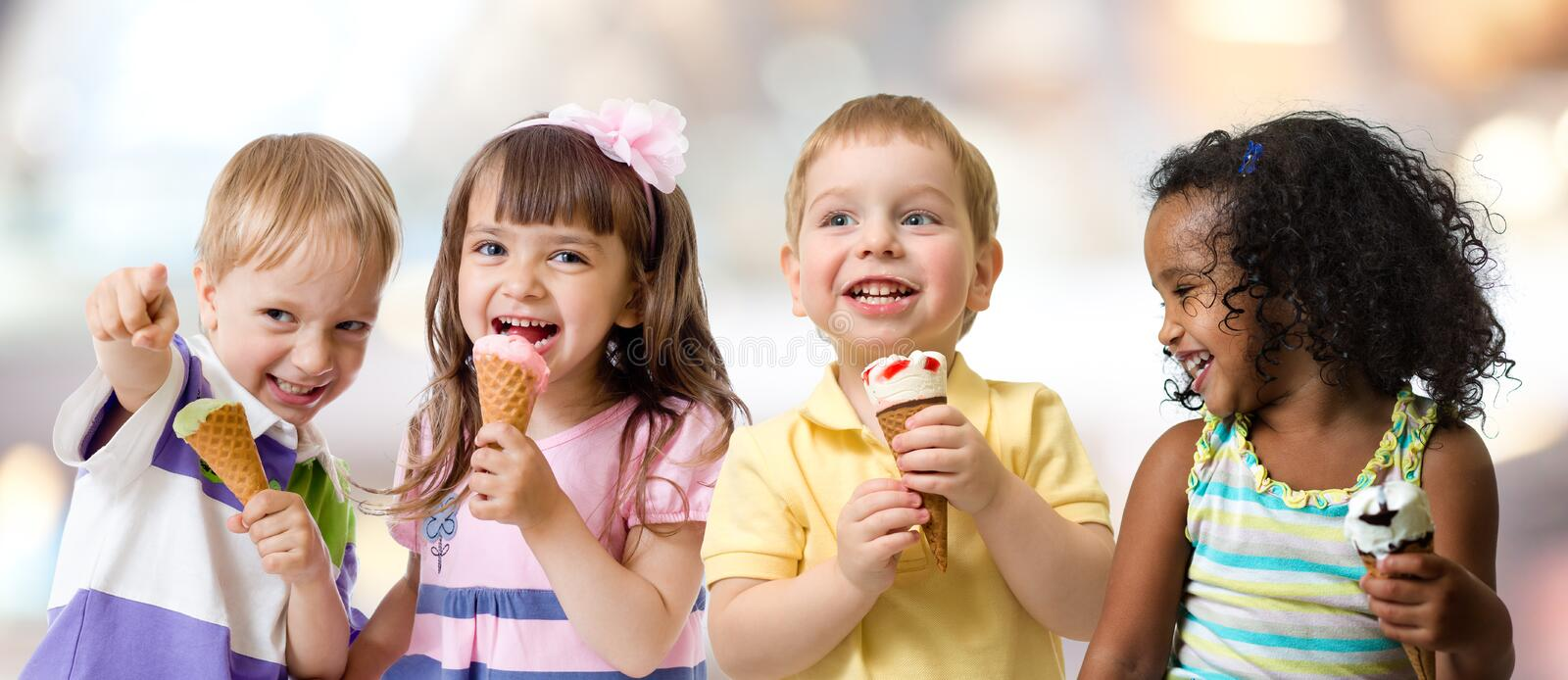 Happy kids group eating ice cream at a party in cafe stock photo