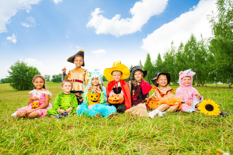 Happy kids in Halloween costumes sit on grass. Happy kids in Halloween costumes sit outside on the grass of field and smile royalty free stock photos