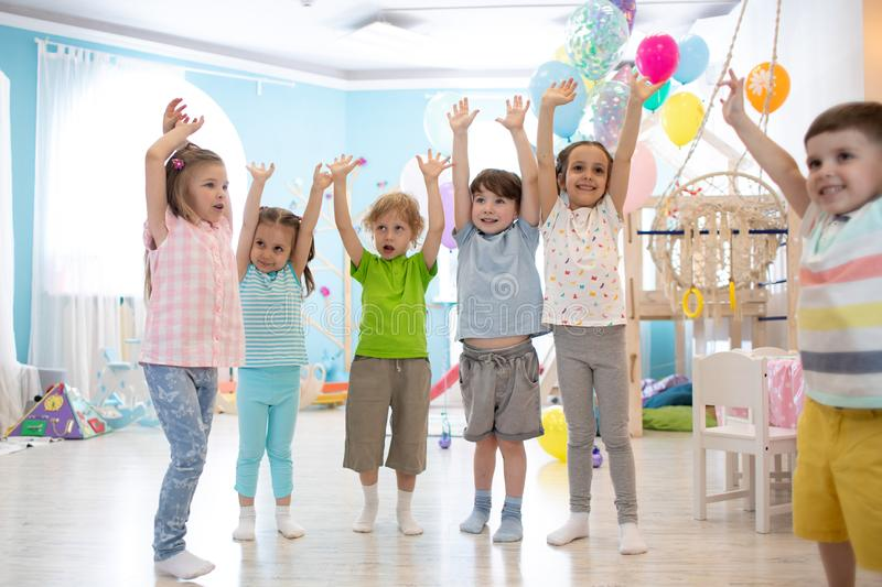 Happy kids with hands up at daycare royalty free stock images