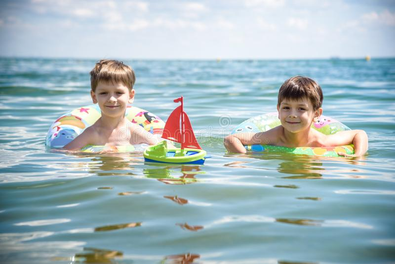Child in swimming pool floating on toy ring. Kids swim. Colorful rainbow float for young kids. Little boy having fun on family royalty free stock photos
