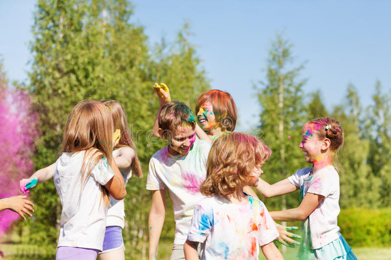 Happy kids having fun with colored powder outside royalty free stock images