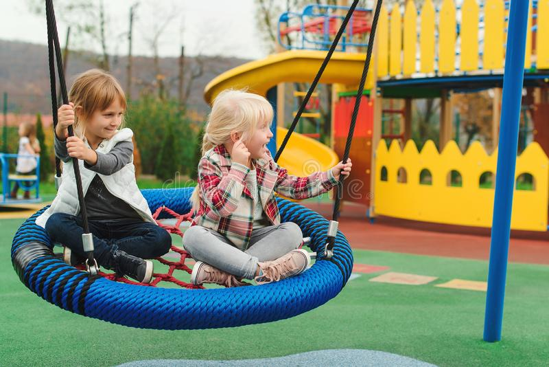 Happy kids having fun on playground outdoors. The best girl friends playing together. Modern colorful playground at park. Playful stock image