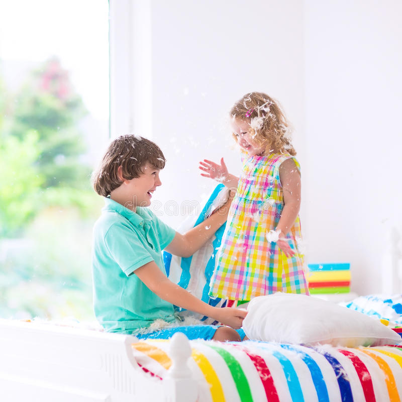 Happy kids having pillow fight. Two children, happy laughing boy and cute curly little girl having fun at pillow fight with feathers in the air jumping, laughing royalty free stock image
