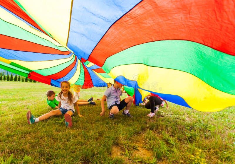 Happy kids hiding under colorful parachute stock images